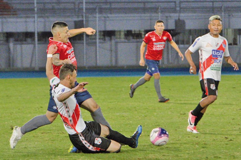 Víctor Galain (piso) disputa el esférico con un rival.