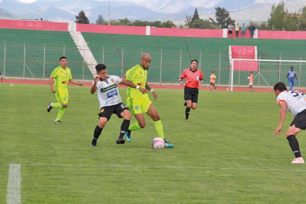 Santos Navarro pelea con un rival la posesión del balón.