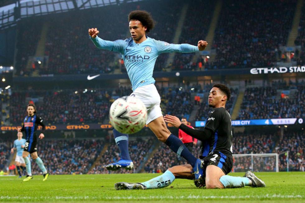 Leroy Sane, de Manchester City, gana la lucha por el balón.