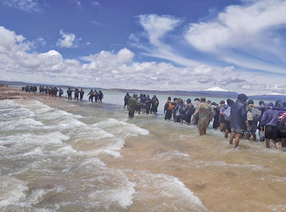 Pasajeros y jóvenes que terminaron el servicio militar pasan sobre el terraplén de Julaca cubierto por el agua.