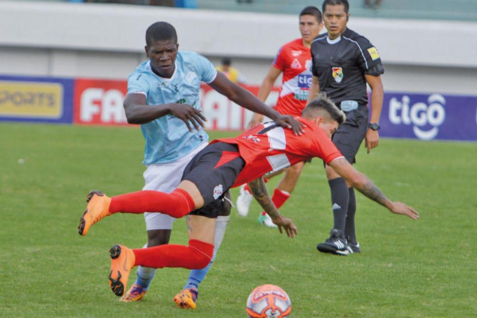 El defensa de Aurora derriba a Nicolás Royón.