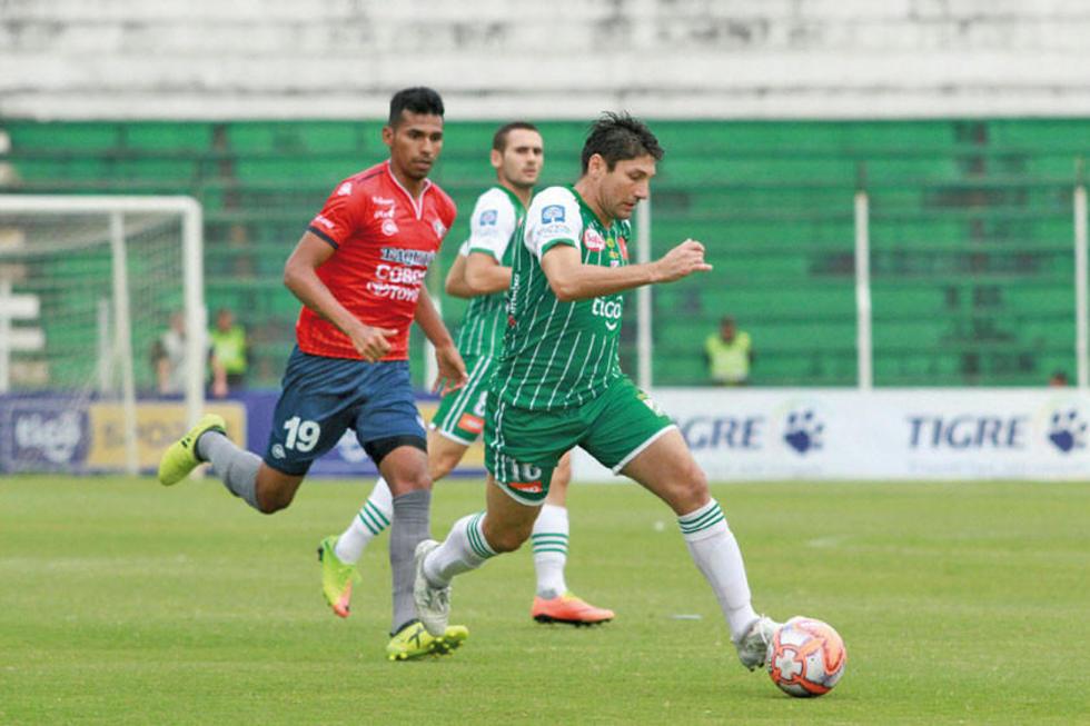 Ronald Raldes sale con el balón ante la presión de Gilbert Álvarez.