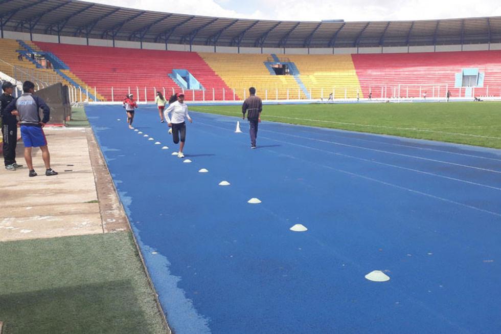 Los atletas trabajan en la pista del estadio.