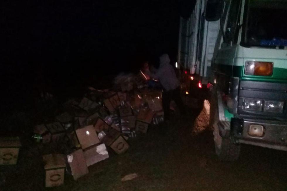 Uno de los delincuentes saca la mercadería de contrabando del camión incautado.