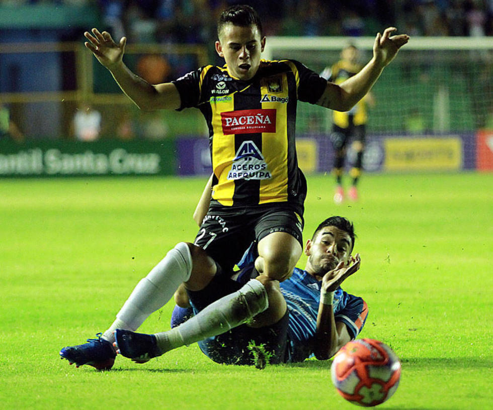 Henry Vaca es derribado por un rival.