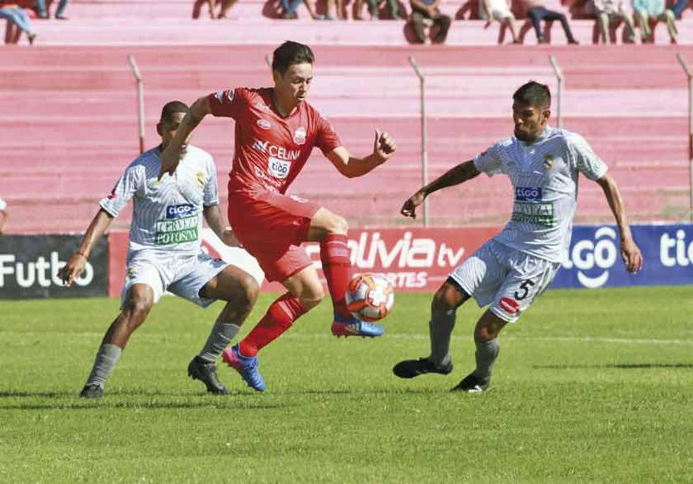 El defensa lila Carlos Tordoya intenta frenar a su rival.
