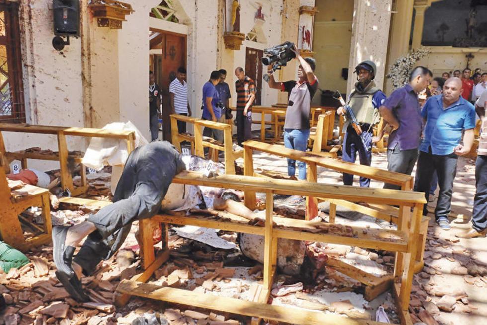 Autoridades y prensa de Sri Lanka inspeccionan uno de los templos donde se produjeron las explosiones.