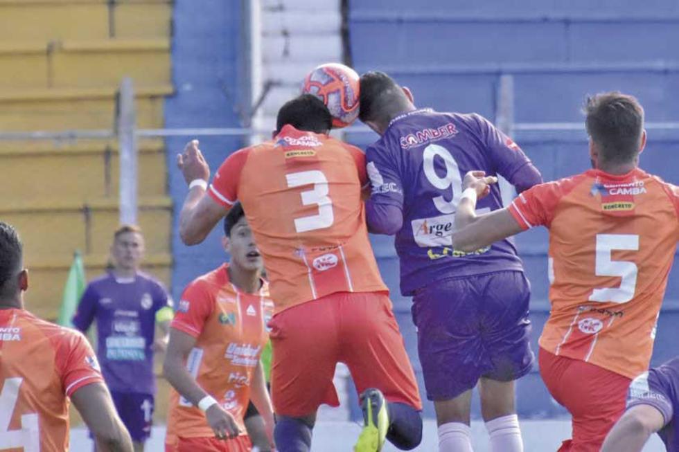 Óscar Velásquez y Juan Vogliotti pugnan el balón en el aire.