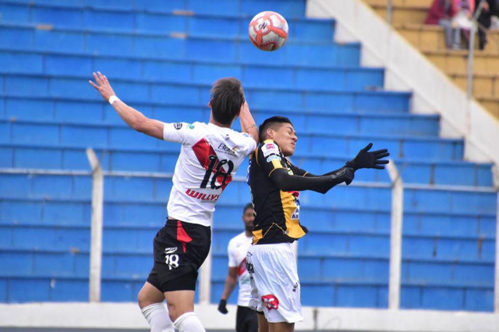 El defensor Víctor Galaín, de la banda roja, cabecea la pelota.