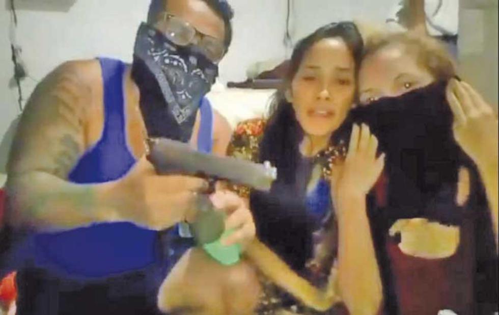 Captura de vídeo de un hombre preso amenazando a dos mujeres.