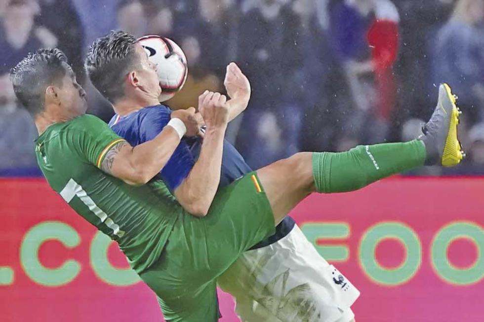 Florian Thauvin, de Francia, y Marvin Bejarano, de Bolivia, pugnan por el balón.