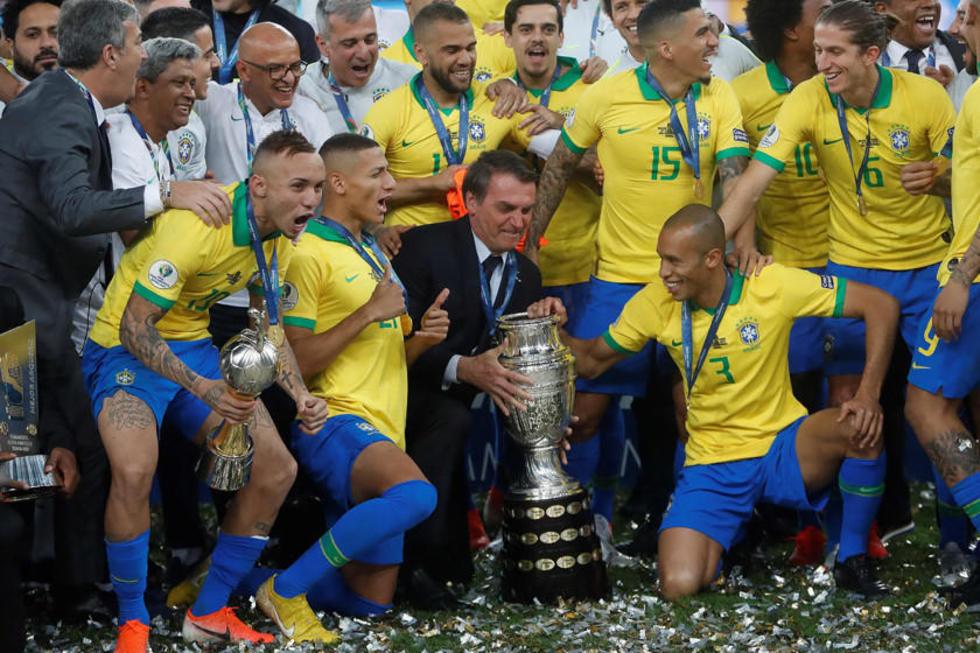 El presidente de Brasil y los jugadores celebran con el trofeo de la Copa América.
