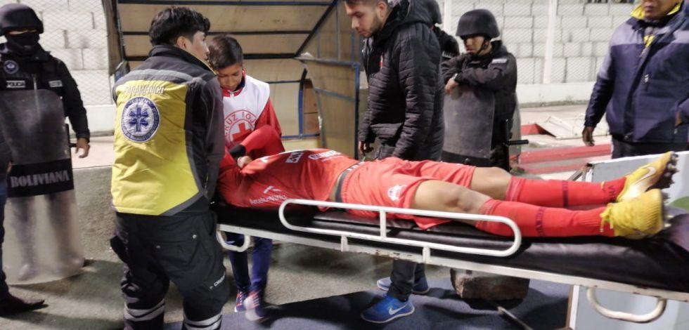 Gonzalo Moruco abandona el campo deportivo en camilla tras un golpe en la espalda.
