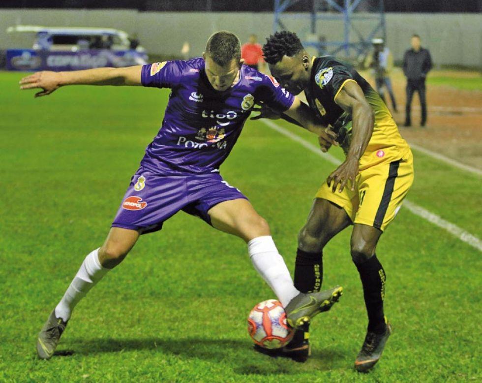 Abraham Cabrera, de Real, protege el balón de un rival.