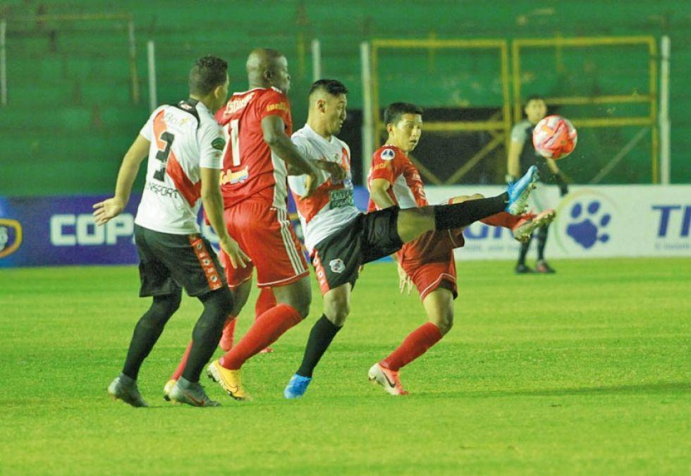 Miguel Quiroga (c) pugna el balón con sus rivales.