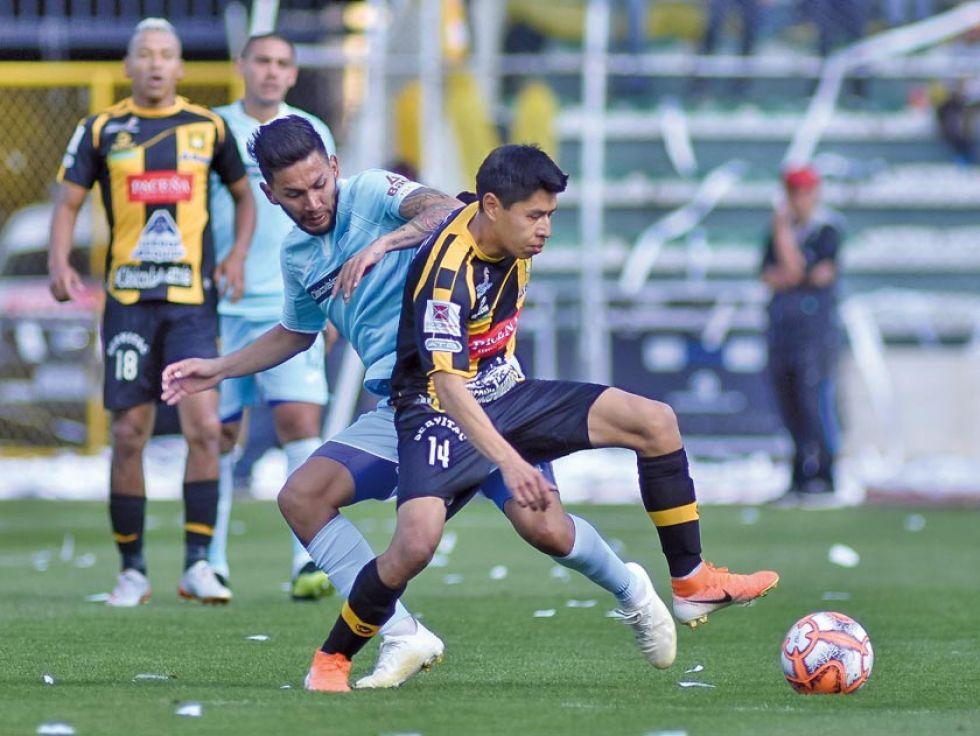 Diego Wayar, del Tigre, gana la pelea por la pelota.