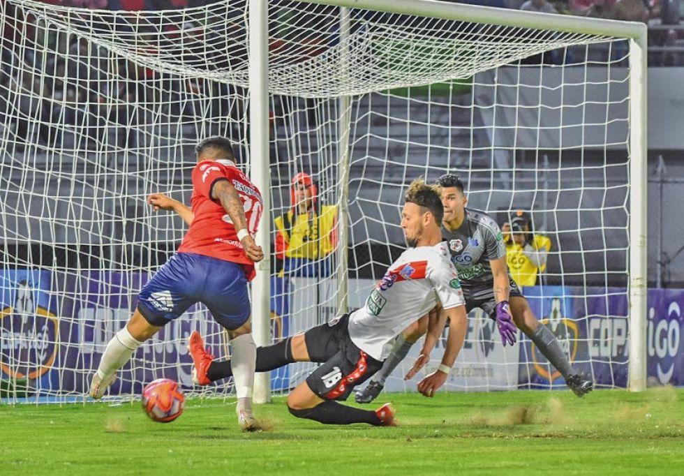 Víctor Galain (c) busca aplacar una de las jugadas ofensivas de los locales.