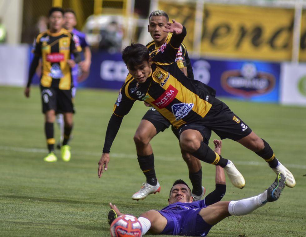 Christian Vargas (piso) trata de detener a su rival.