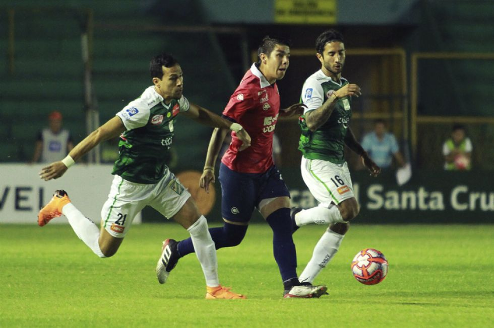 Julio César Pérez y Sebastián Gamarra tratan de detener al jugador cochabambino.