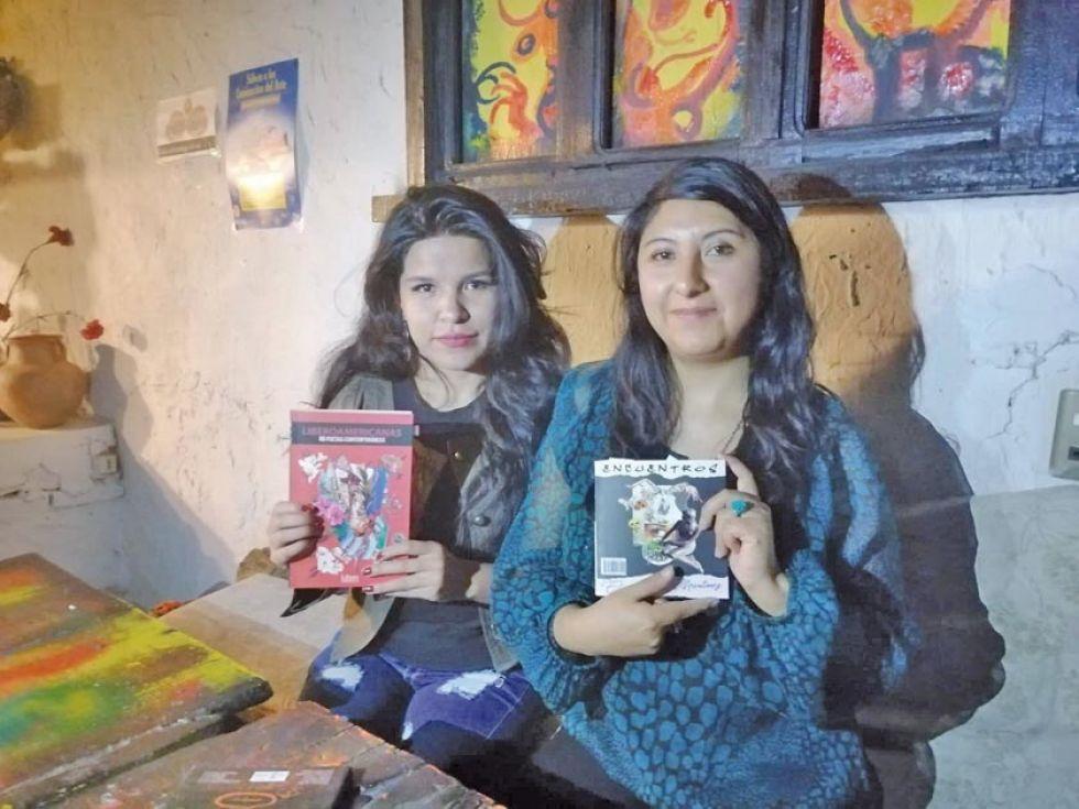 Sarah y Eliana muestran, cada una, uno de sus libros.