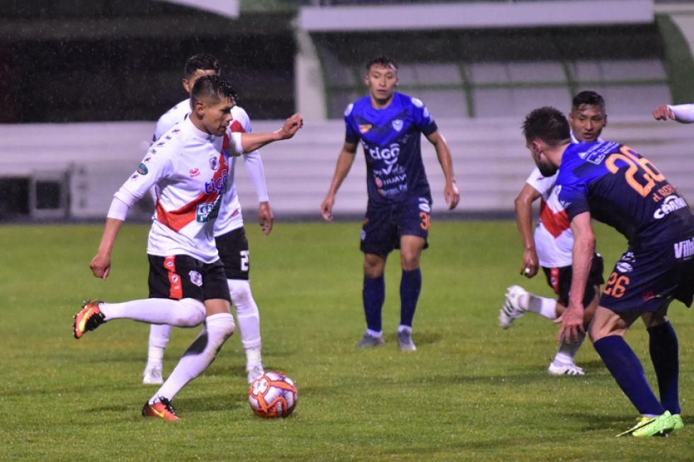 Luis Torrico trata de pasar la marca de sus rivales.