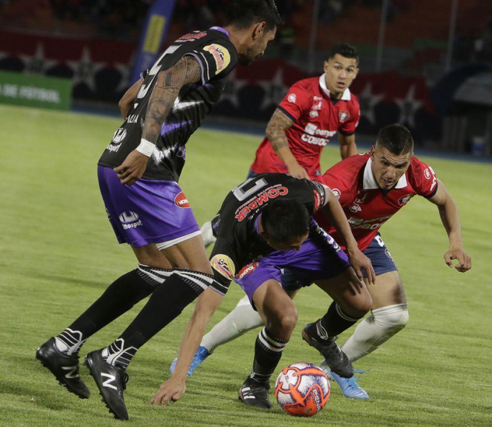 Christian Vargas, de Real, protege el balón ante la entrada brusca de Juan Aponte, de Wilster.