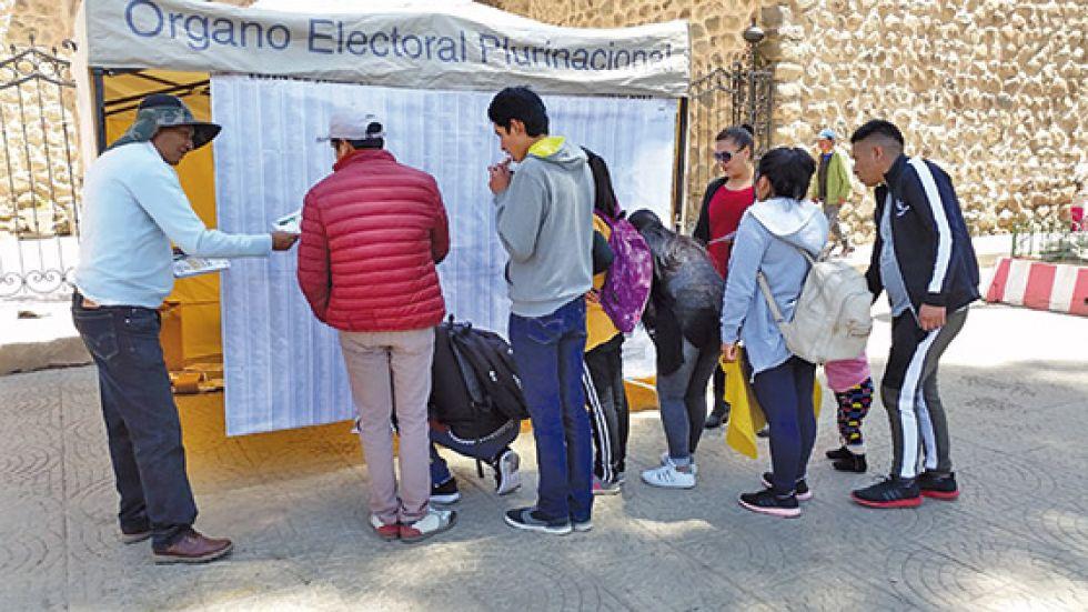 Los ciudadanos verifican su recinto y mesa de votación.