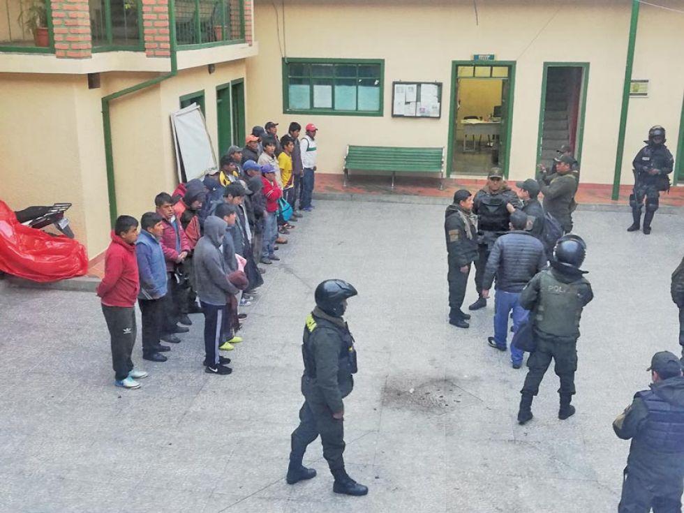 Vista general de los arrestados y policías.