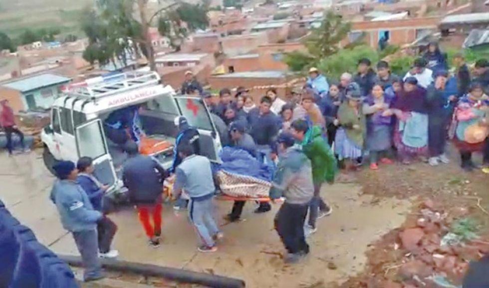 Pobladores introducen el cuerpo del fallecido a una ambulancia.