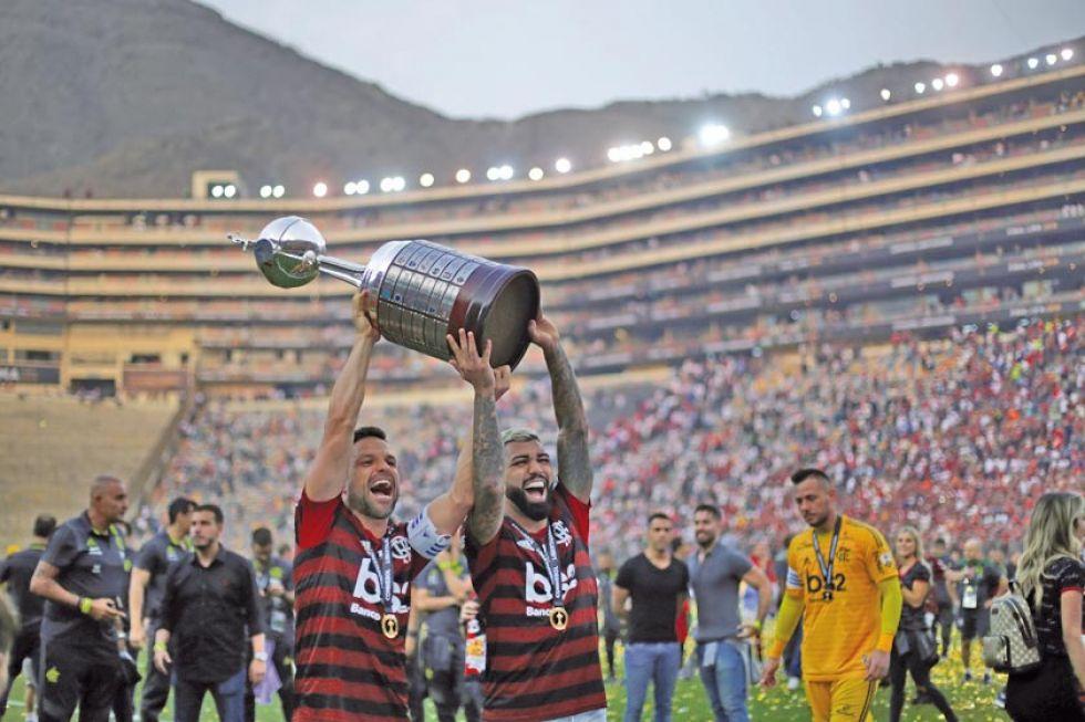 Everton Ribeiro (i) y Gabriel Barbosa de Flamengo celebran con el trofeo de campeones.