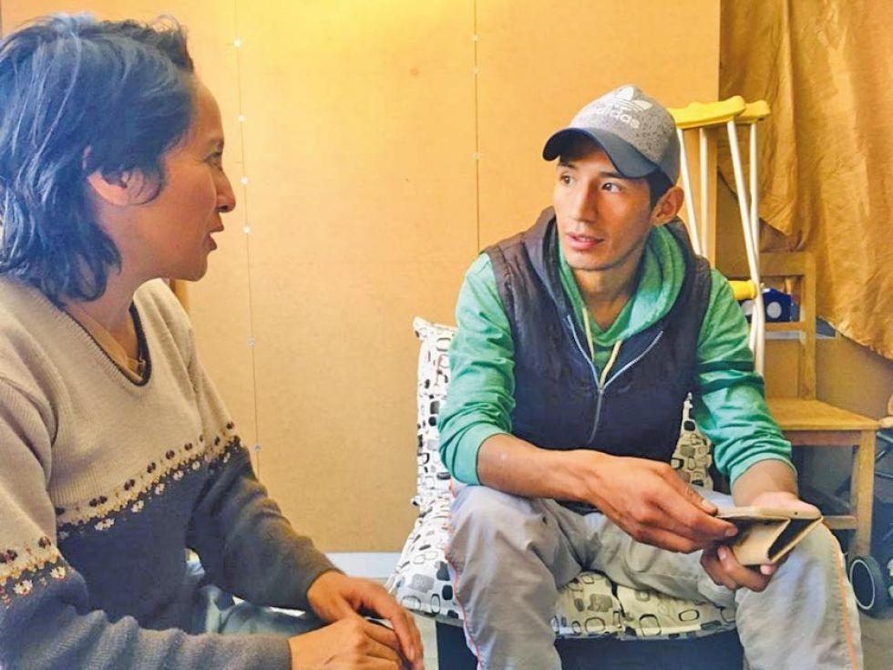 Azucena Fuertes habla con Darío Cuiza, quien se moviliza con muletas.