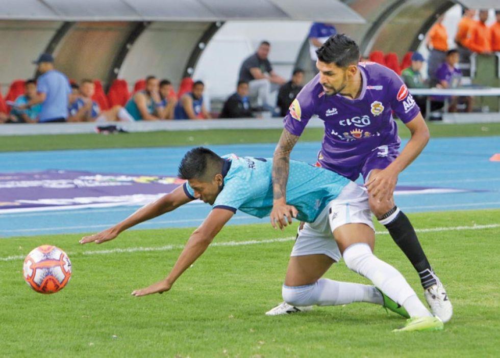 Carlos Hugo Tordoya (d), de Real, marca a su rival.