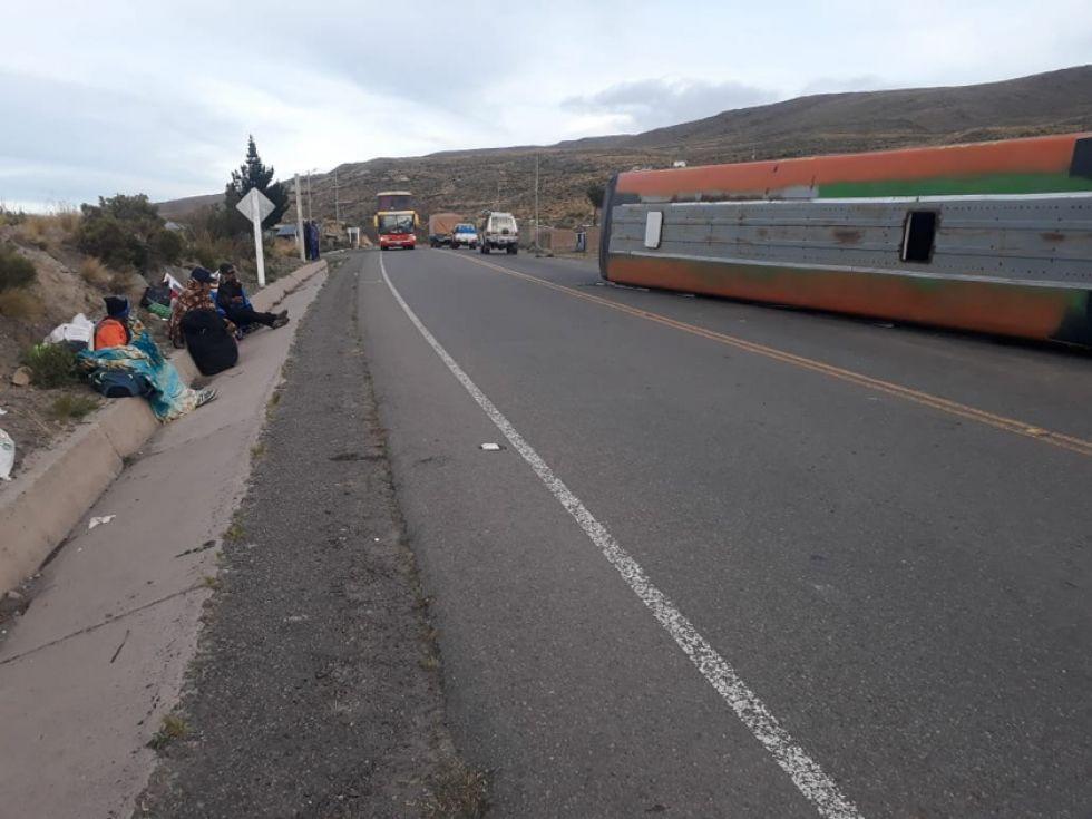 Así quedó el bus. Los pasajeros ilesos aparecen a un lado de la carretera.