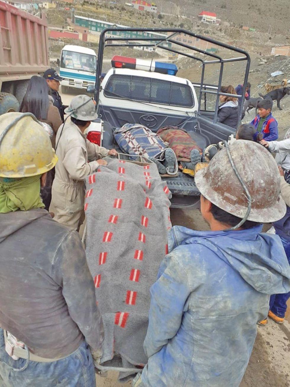 Los restos de los tres hermanos son subidos a una camioneta policial.