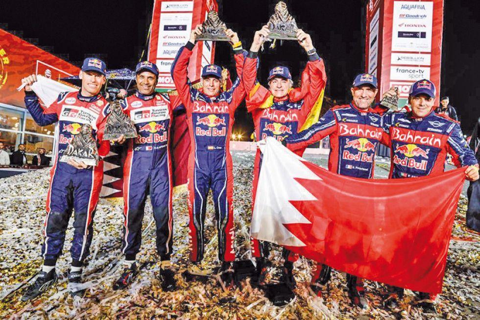 Los ganadores en la categoría autos levantan sus trofeos en el podio.