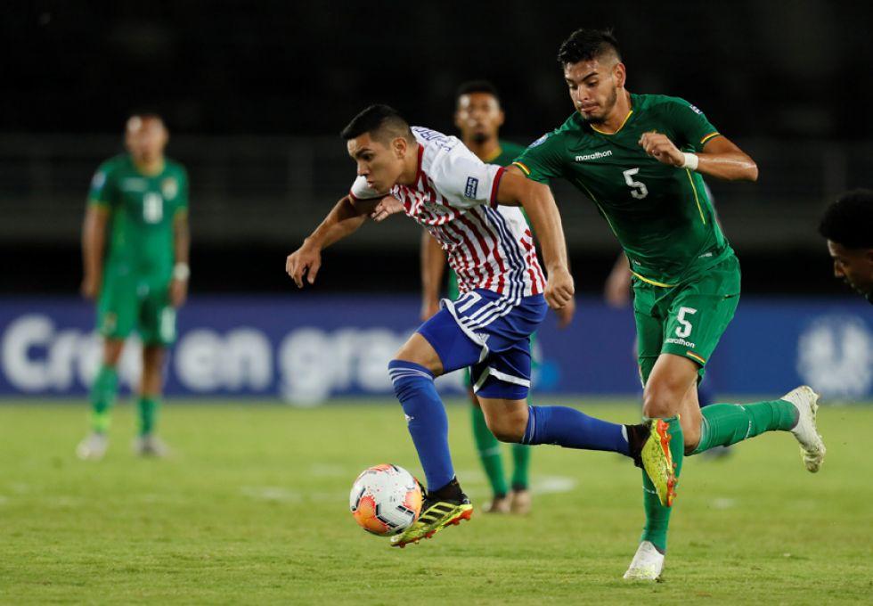 Hugo Fernández, de Paraguay, disputa un balón con José Carrasco, de Bolivia.