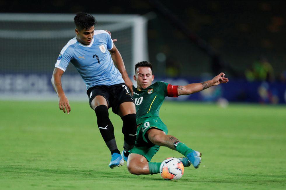 Henry Vaca (d), de Bolivia, disputa un balón con Douglas Arezo, de Uruguay.