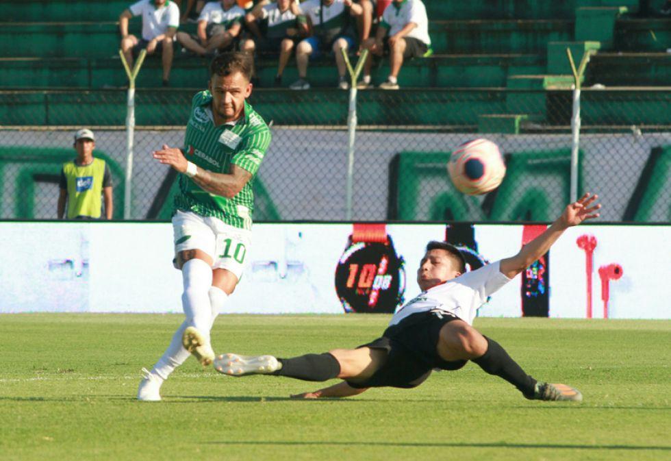 Matheo Zoch patea el esférico pese a la marca de un rival.
