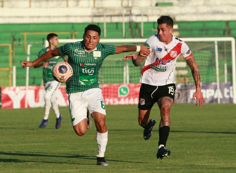 Daniel Rojas y Miguel Suárez pelean por el balón.