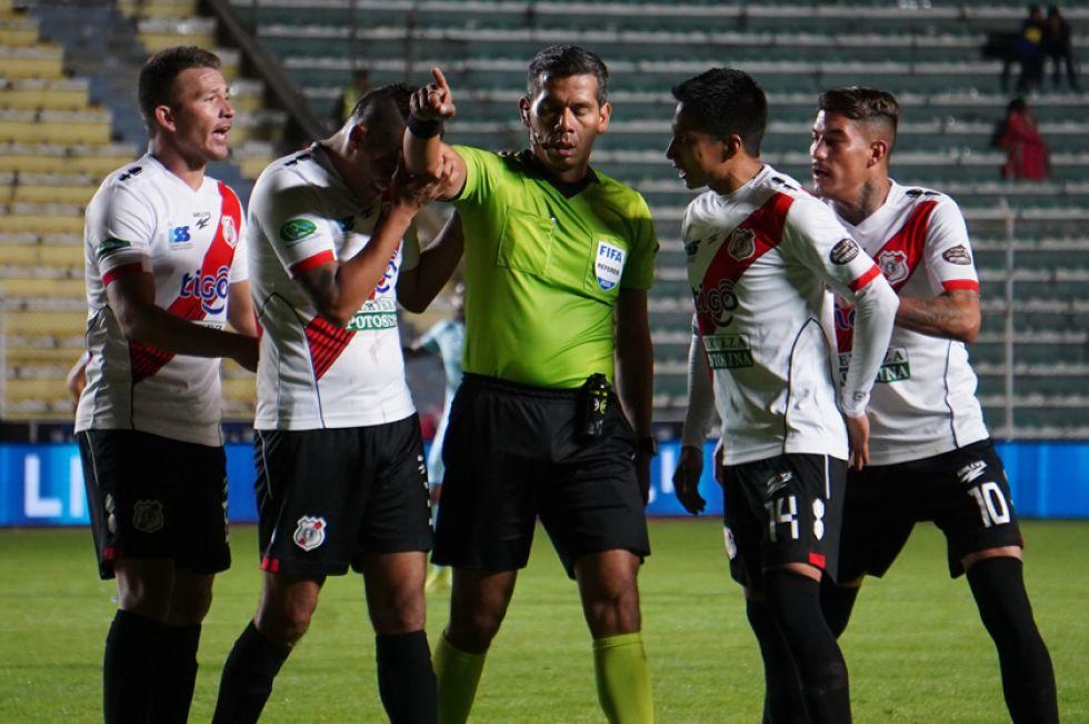 Los jugadores de Nacional reclaman al árbitro una de sus decisiones.