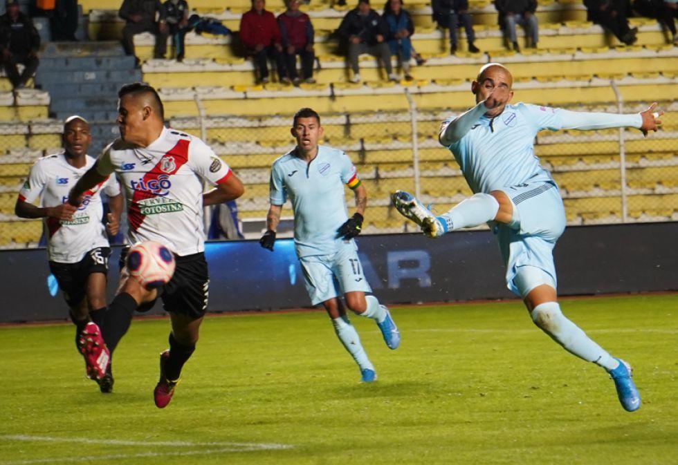 Jorge Cuéllar (i) trata de bloquear el disparo de Marcos Riquelme.
