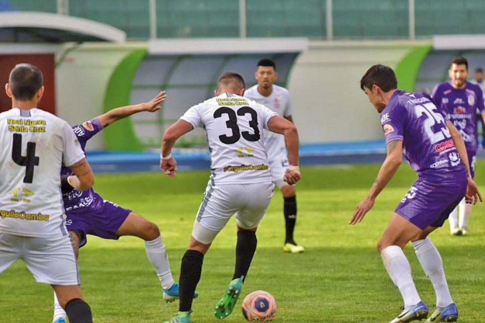 El zaguero Juan Rivero (c) sale ante la marca de dos jugadores de Real.