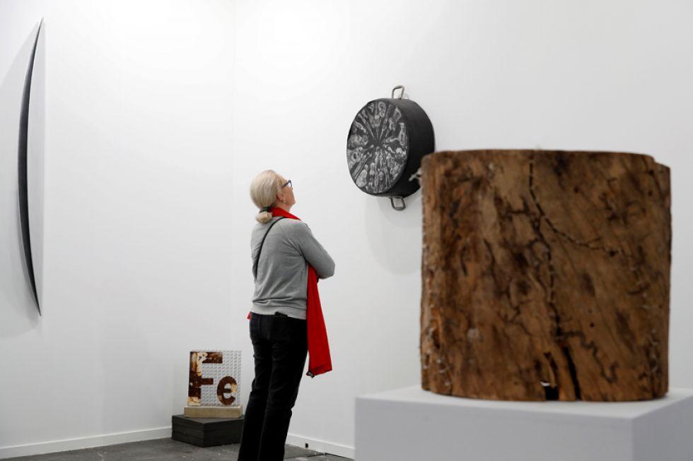 Una mujer observa obras de Elio Jsús Fonseca y David Rodríguez.