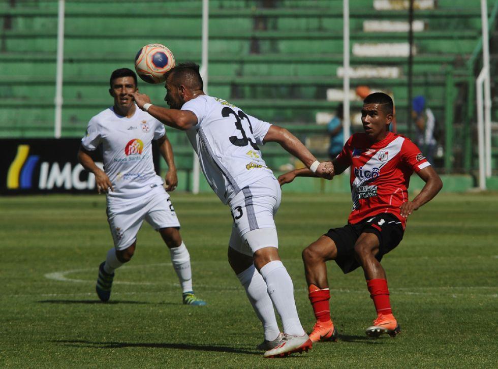 Juan Rivero (c) cabecea el balón ante la presión de un rival.