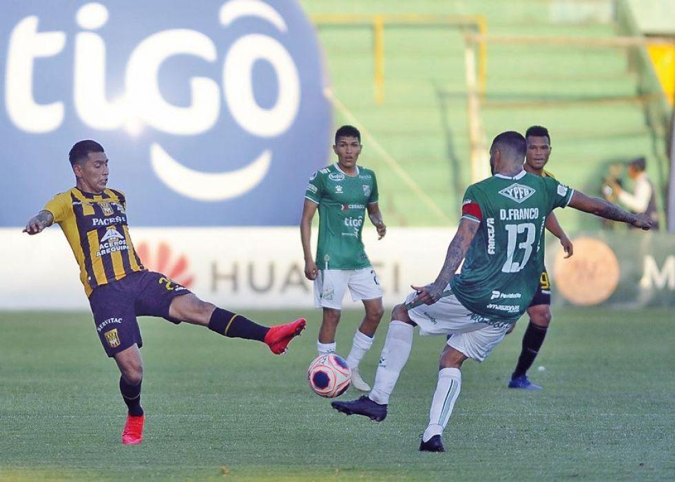 Daniel Franco (d) remata el balón ante la resistencia de un rival.