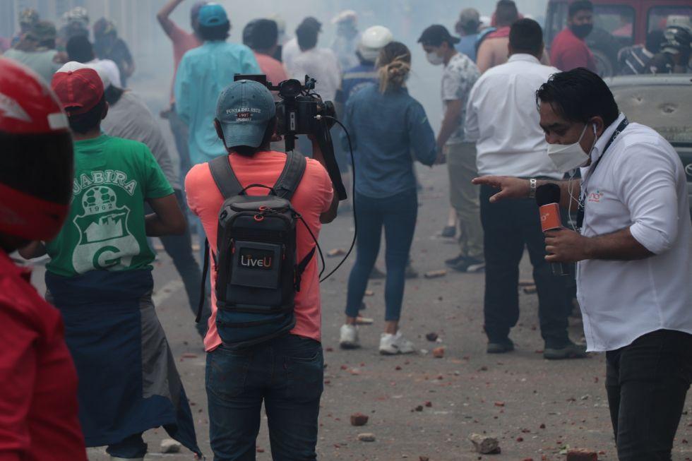 Un periodista del equipo de prensa de la red de televisión privada Red Uno transmite en directo los incidentes por la disputa de la administración municipal