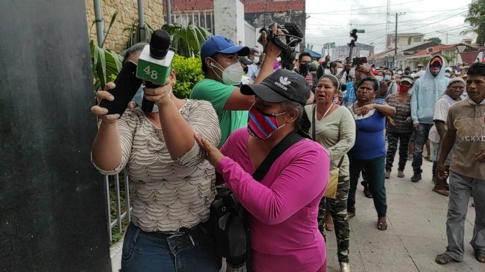 La periodista de Canal 48 de la ciudad de Montero, Vivian Pérez, trata de protegerse del ataque de padres de familia
